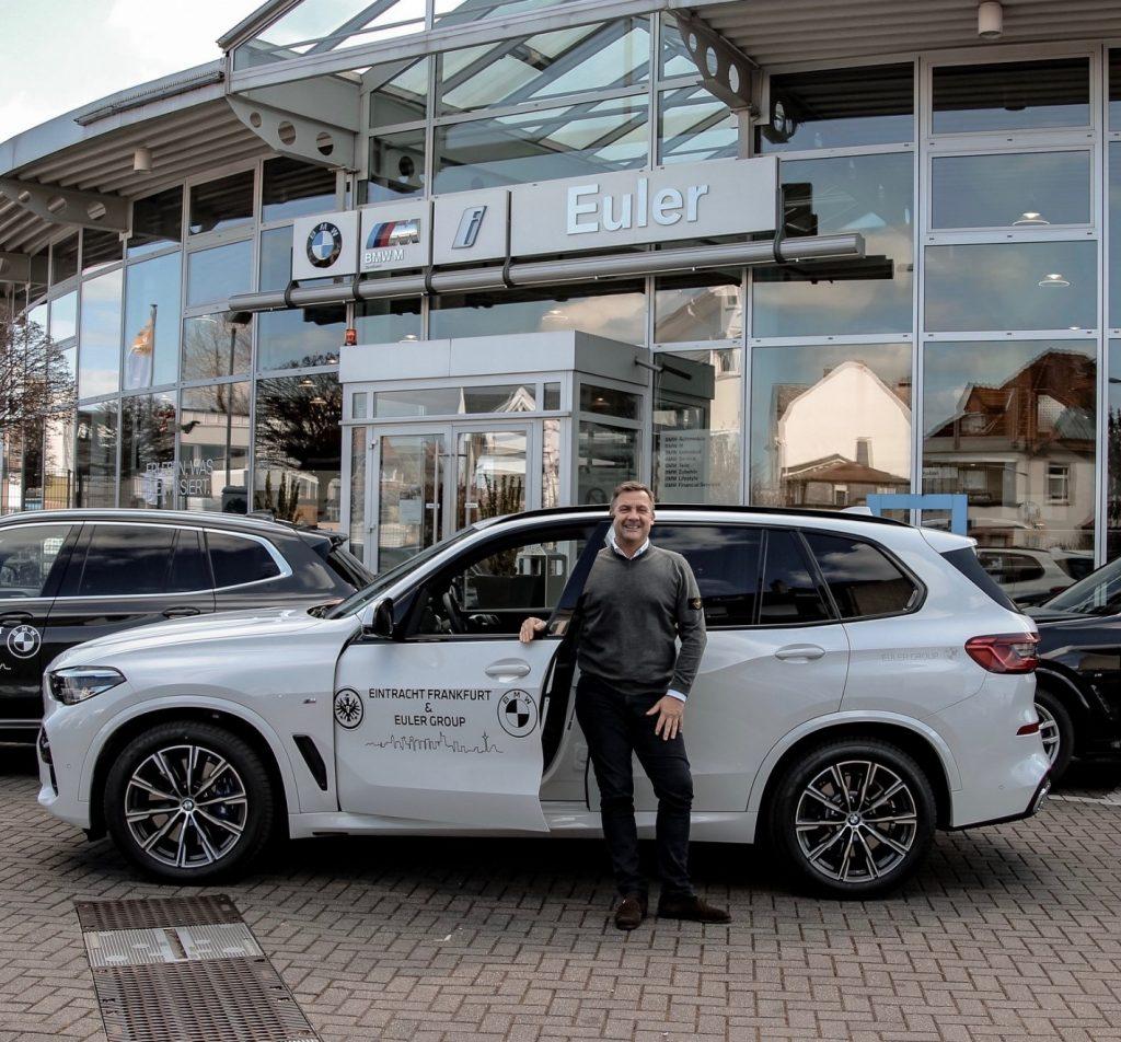 Freiherr Cyril von Recum vor einem der drei Fahrzeuge aus dem Hause BMW EULER, die aktuell für besonders gefährdete Eintracht-Mitglieder auf den Straßen Frankfurts unterwegs sind.